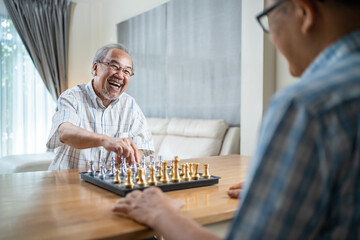 Asian old man enjoy playing chess together with friend in nursing home