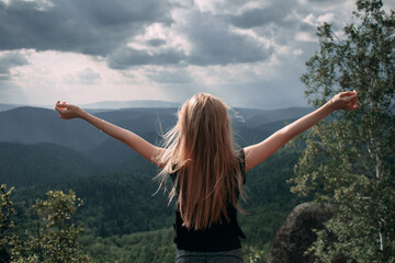Young blond girl with hands up enjoing view of the evergreen taiga forest hills on rainy day. Stolby Nature Reserve in Krasnoyarsk, Russia.