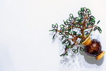 Handmade tree made of black and green beads and copper wire in a clay jar with a shadow on a light background with an empty space for inserting text. Product made of beads for home decoration.
