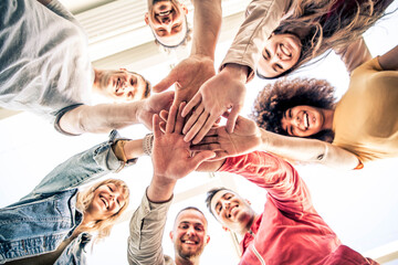Young happy people stacking hands together outcoor - Community of multiracial international people supporting each other - Diverse culture