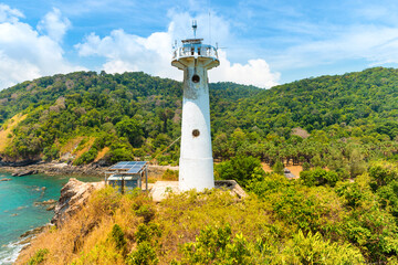Lighthouse on green coast. Sea lighthouse beacon on rock, Koh Lanta, Thailand