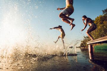 Friends having fun enjoying a summer day swimming and jumping at the lake.
