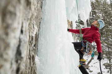 Man climbing ice wall in mountains