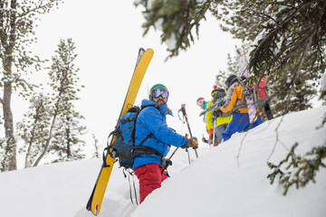 Male backcountry skier hiking with friends in mountains