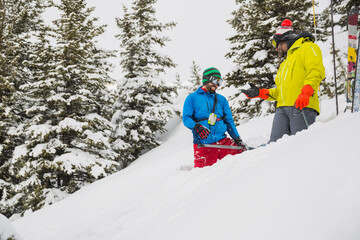 Male backcountry skiers shoveling snow in mountains