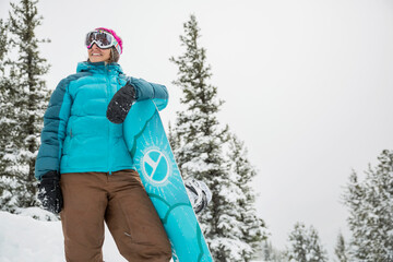 Smiling woman snowboarder in mountains