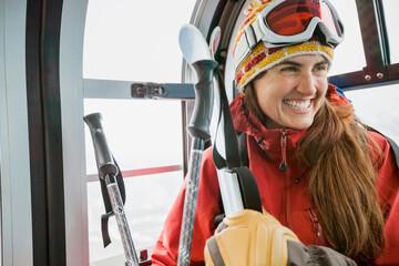 Smiling female skier in gondola