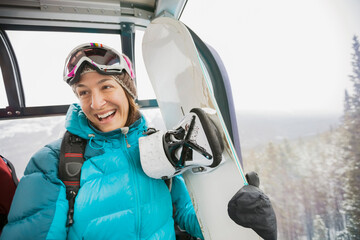 Smiling female snowboarder in gondola
