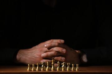 Man playing chess on dark background, closeup