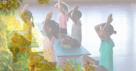 Composition of children practicing yoga on yoga mats in fitness class with tree overlay