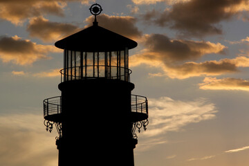Silhouette of old lighthouse tower on a stunning sunset almost nightfall sky  to look for seafood and navigation for boats and guidance of ships