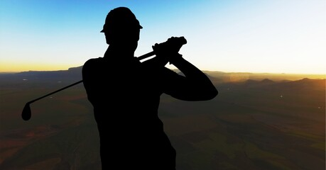 Composition of silhouette of male golf player over landscape and blue sky with copy space