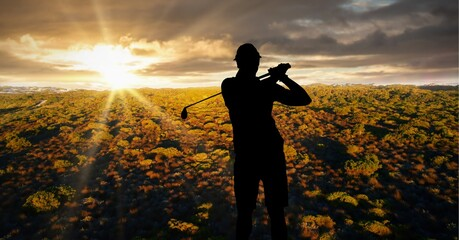 Composition of silhouette of male golf player over landscape and sunset