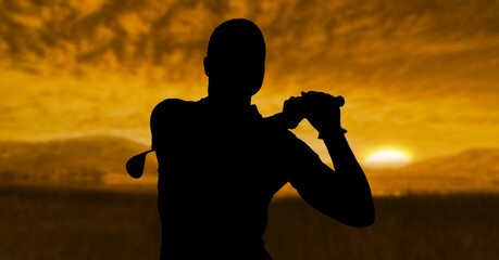 Composition of silhouette of male golf player over landscape and sun setting with copy space