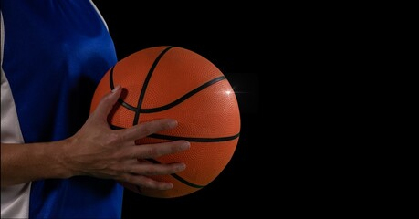 Composition of midsection of male basketball player with ball and copy space on black background