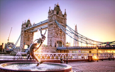"""Girl With A Dolphin Fountain"""" by English artist David Wynne in front of the tower bridge in London, UK"""