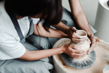 Modeling a pot on a potter's wheel. Male and female hands close up. A date in a hobby workshop