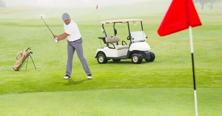 Composition of caucasian man playing golf striking with golf club next to golf cart