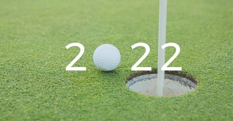 Composition of 2022 number with golf ball by hole on golf course