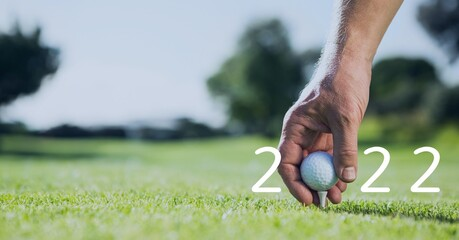 Composition of 2022 number with golf ball placed by man on tee on golf course