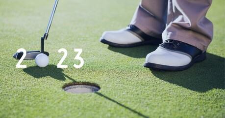Composition of 2023 number with golf ball and player with golf club on golf course