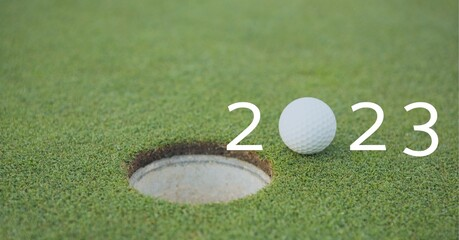 Composition of 2023 number with golf ball by hole on golf course