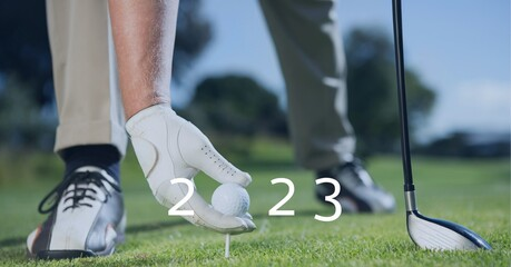Composition of 2023 number with golf ball placed by golf player on tee on golf course