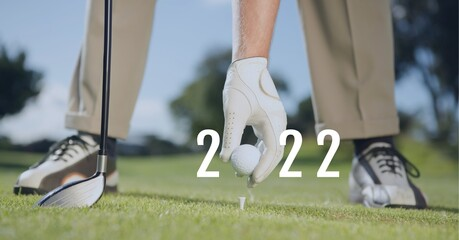 Composition of 2022 number with golf ball placed by golf player on tee on golf course