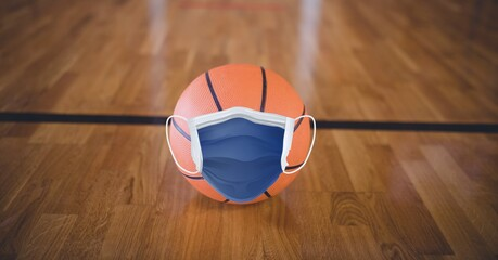 Composition of basketball with face mask on basketball court with copy space