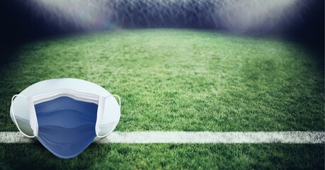 Composition of american football with face mask on grass with copy space