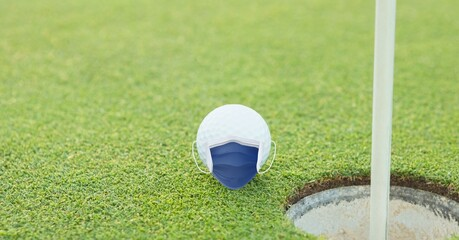 Composition of golf ball with face mask on grass with copy space
