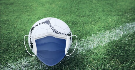 Composition of football with face mask on grass with copy space