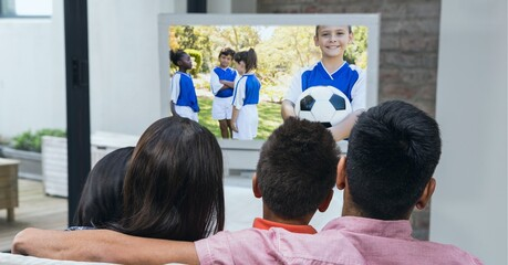 Compostion of family watching diverse children playing football on tv at home
