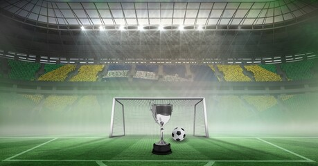 Compostion of cup and football over stadium and goal