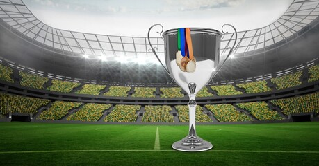 Compostion of cup and medals over football stadium