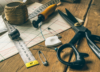 closeup view of retro sewing tools, scissors, chalk, measuring tape lie on tailors' diagrams and wooden table