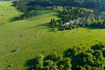Top view aerial photo: farmer's house in a beautiful mountain forest with a large green meadow. travelers at a halt with smoke from a campfire, a large field in the taiga