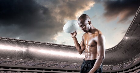 Shirtless african american male rugby player holding a rugby ball against stadium in background