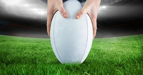 Close up of hands placing a rugby ball on grass field against stadium