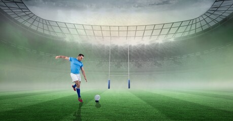 Caucasian male rugby player kicking the rugby ball against stadium in background