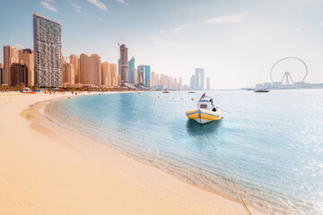 Boat moored to the pier and the largest Ferris Wheels in the World is the Dubai Eye. Top tourist attractions in the United Arab Emirates
