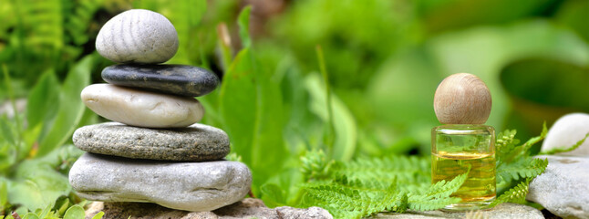 essential oil bottle next to a pile of  pebbles among green foliage in garden