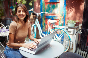 beautiful young woman sitting in outdoor cafe with her laptop on table, smiling looking at camera.