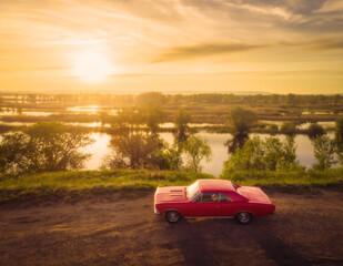 Red retro classic muscle car on the road near river at sunset