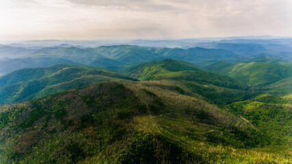 View from above. Russian green taiga. Green ridge of a high mountain, overgrown with conifers.