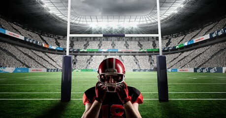 Composition of male american football player holding helmet at stadium