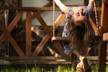 Close up portrait of beautiful young girl sitting on the swing upside down. Concept of happiness. Copy space.