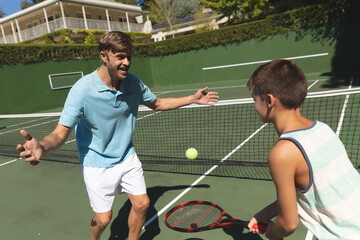 Happy caucasian father and son outdoors, playing tennis on tennis court