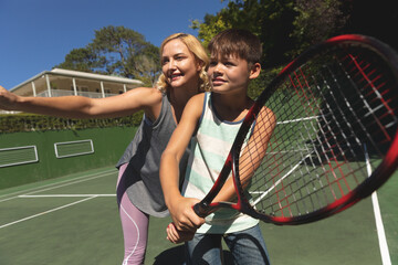 Caucasian mother and son outdoors, playing tennis on tennis court