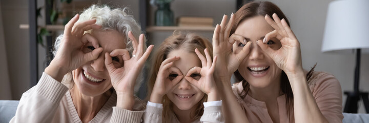 Having fun with mommy and granny. Funny family portrait of three women generations older grandmother grownup mother and little daughter look at camera through cute glasses of fingers. Web banner image